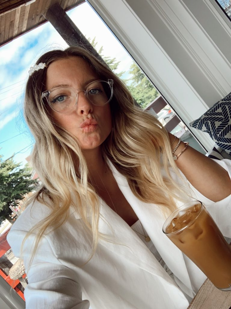 Lifestyle blogger, Sydney Socias wears hair clip and clear framed glasses in selfie at coffee shop.