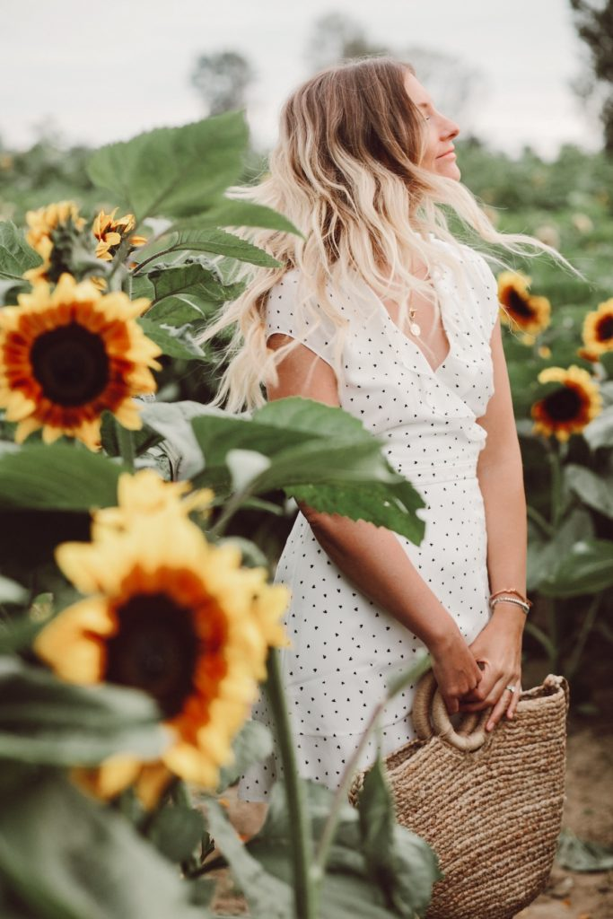 Girl wearing sundress in field of sunflowers at Richmond Sunflower Festival.